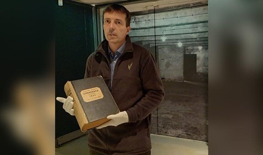 <p>De directeur van het Oorlogsmuseum in Overloon met het Dodenboek van Auschwitz.</p>