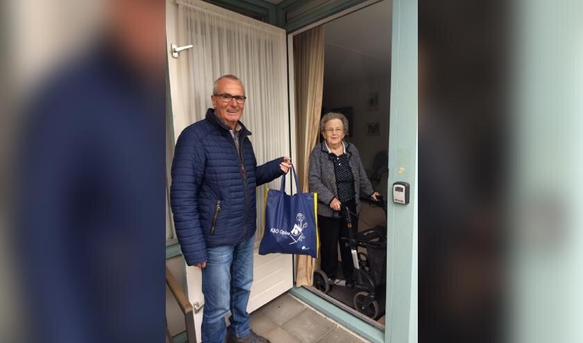 Foto KBO Oploo. voorzitter Jan Peeters overhandigd tas aan mevr. Marietje Fransen-Verlienden.