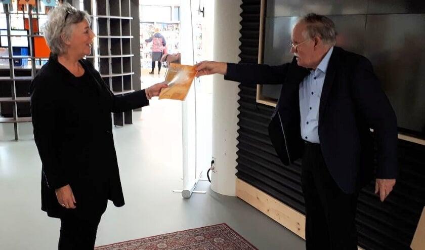 <p>Schrijver Adriaan Sanders reikt het eerste boekje uit aan Karin van de Ven.</p>