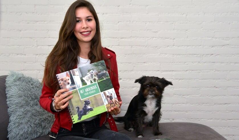 <p>Een trotse Joy met haar boek in haar handen en haar hondje naast haar. (foto: Henk Lunenburg)</p>