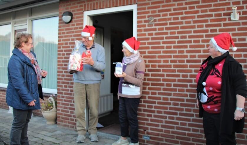 <p>Links dirigente Els Thijssen en rechts Nelly van de Heuvel. Ze verrassen de koorleden Peter en Maria Claassen.</p>
