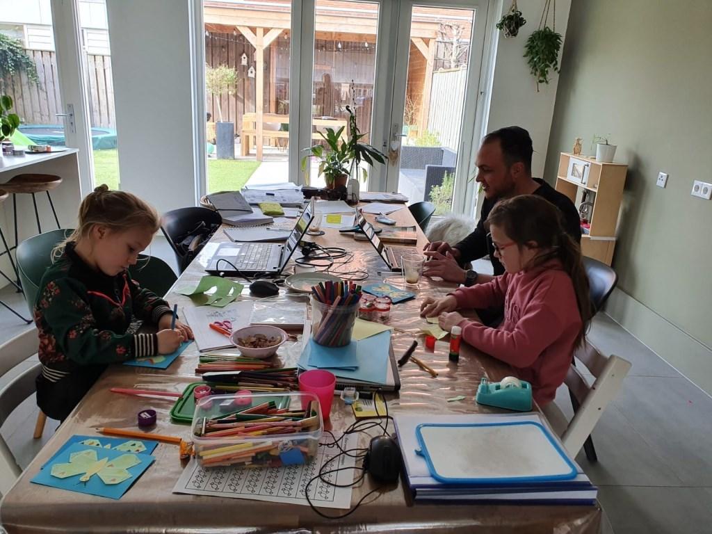 Lis, Lot en vader Nikky zijn hard aan het werk aan de keukentafel.   © Kliknieuws Veghel