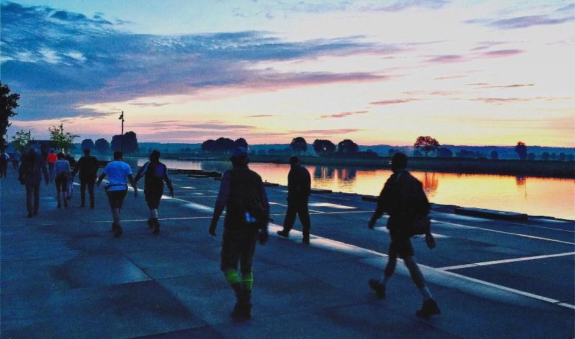 Deelnemers aan de vorige 80 Land van Cuijk lopen in alle vroegte langs de Maas bij Cuijk. (foto: Robert Cooijmans)