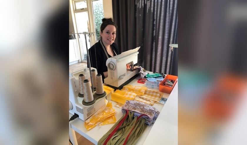 Merel Vesters-van Bree (34) naait thuis herbruikbare mondkapjes voor zorginstanties in Uden.
