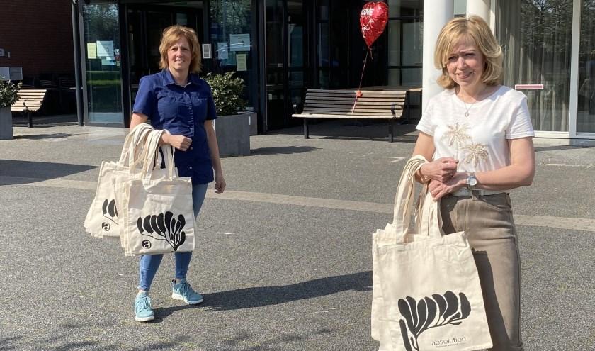 Diana van Dijk-Roelofs (r) overhandigt de Absolution verwentassen aan Wilma Vervoort (l) van de Watersteeg.