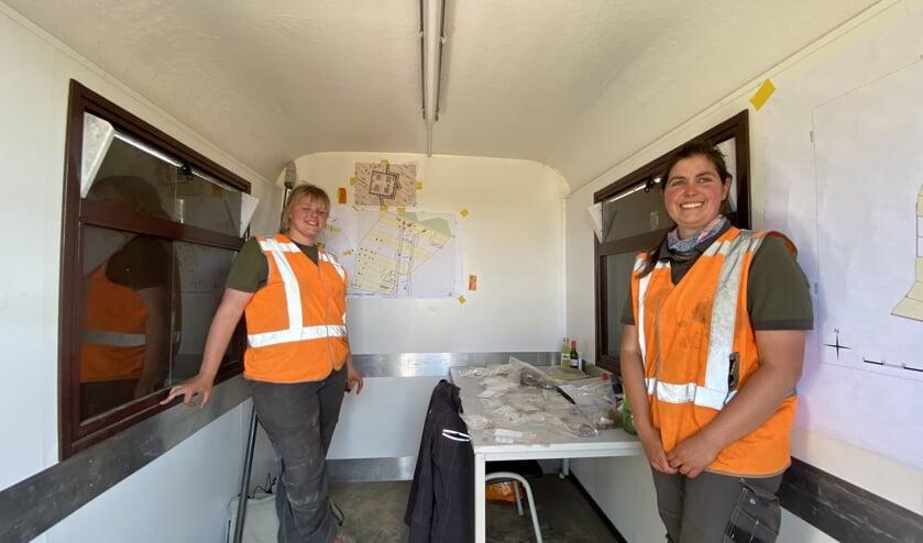 De archeologen Pleun Beurskens (achter) en Emma de Boo van Uijen tonen de vondsten. Op de achterwand overzichtskaarten waarop het kamp getekend is. (foto Jos Gröniger)