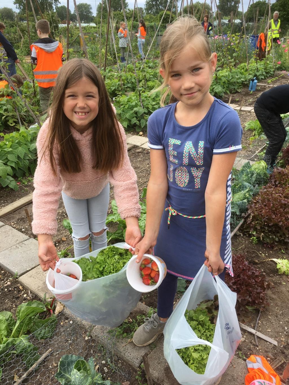 De enthousiaste tuiniersters Ilse en Mirre zijn trots op hun oogst.