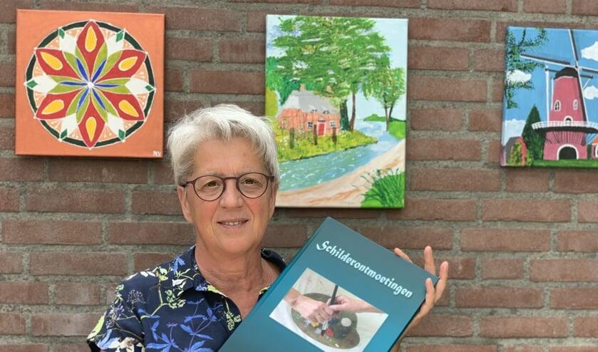 Diny Lamers met haar boek Schilderontmoetingen.