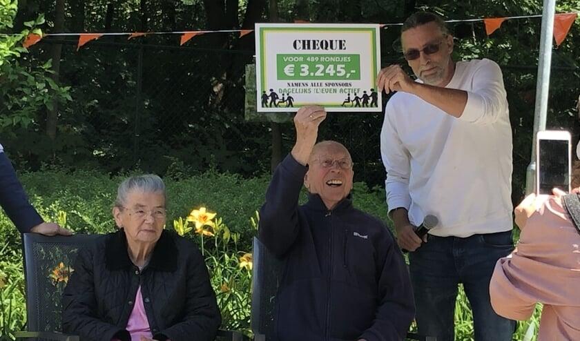 Jan Simons (94) steekt trots de cheque de hoogte in. Naast hem staat locatiemanager Rob Paulussen.