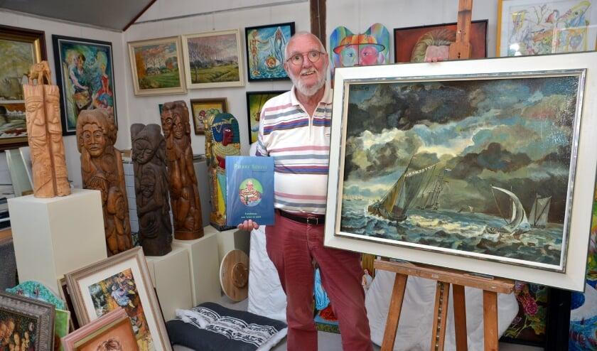 Pierre tussen zijn kunstwerken, met zijn boek in zijn hand. (foto: Henk Lunenburg)