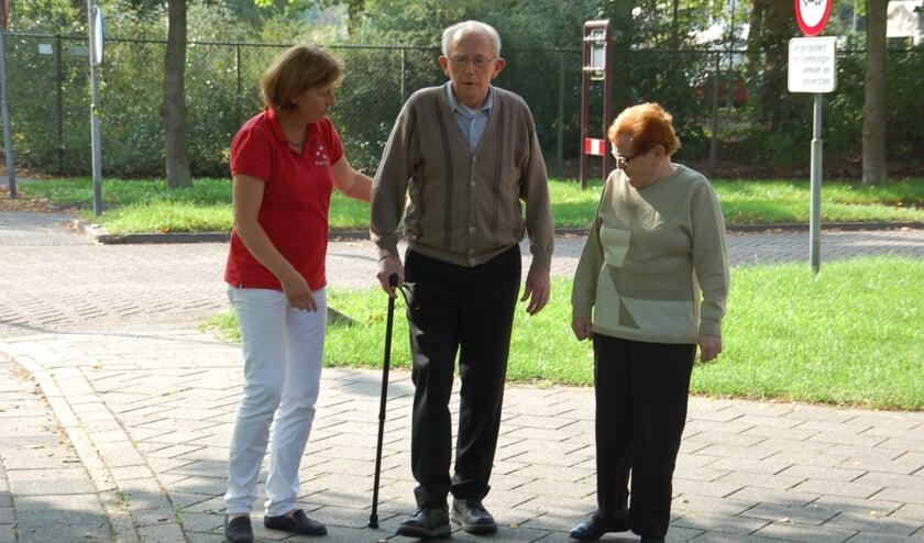 Marian op een archieffoto met een patiënt die uitleg krijgt over het lopen met een stok.