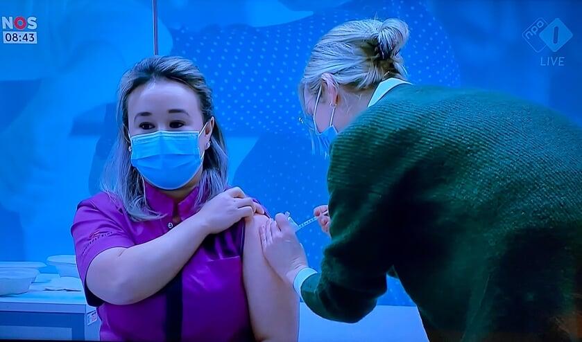 <p>Sanna krijgt het eerste vaccin toegediend.</p>