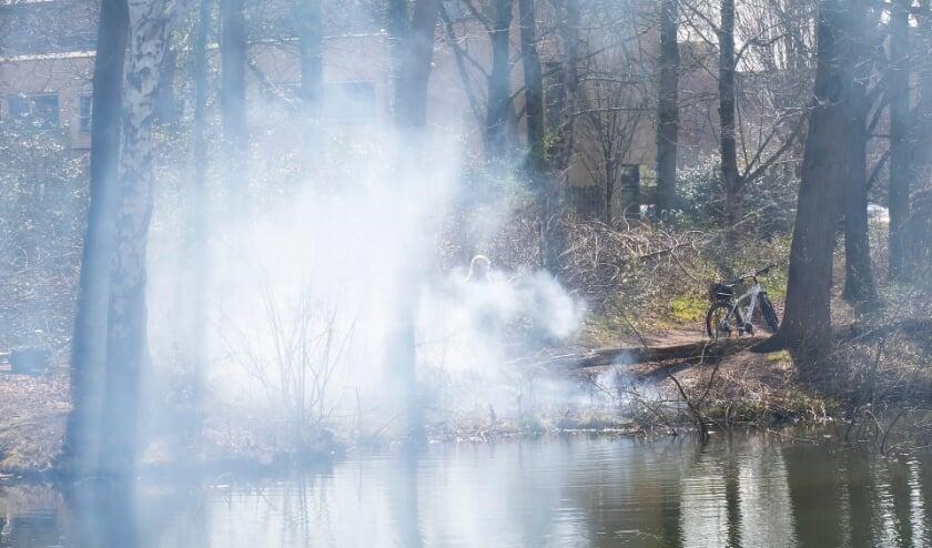 Politieman en handhaver blussen buitenbrand in Joost van den Vondellaan. (Foto: Gabor Heeres, Foto Mallo)