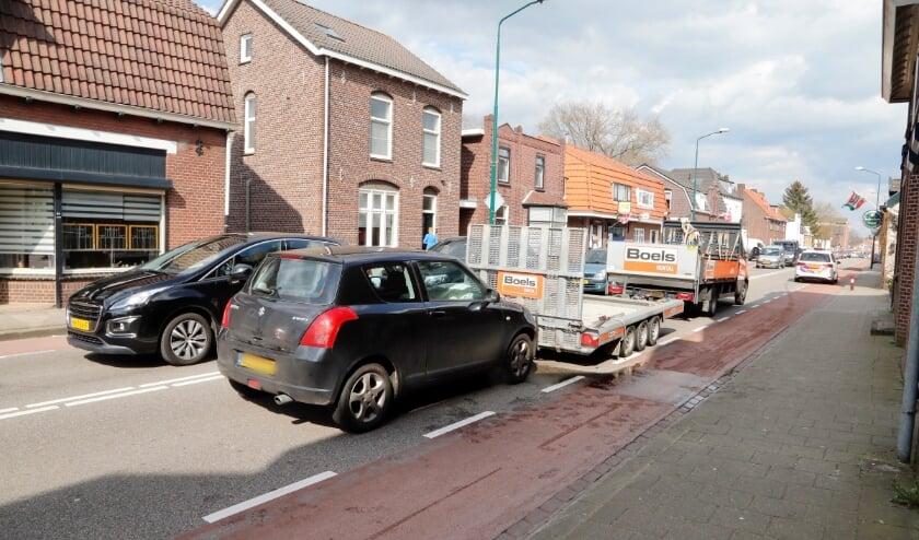 Een zwarte Suzuki botste achter op een wagen met aanhanger.