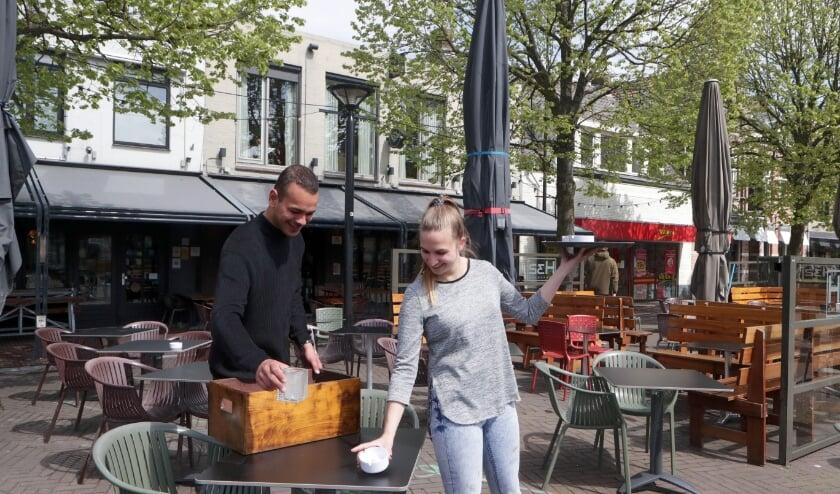 <p>Medewerkers van restaurant H32 maken het terras gereed.</p>