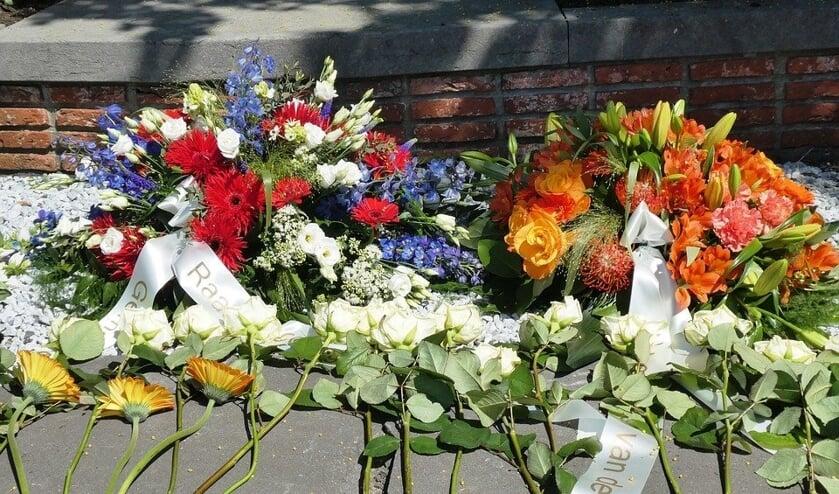 Burgemeester Teunissen legt op 4 mei een krant bij het monument op het Vrijheidsplein in Gennep.