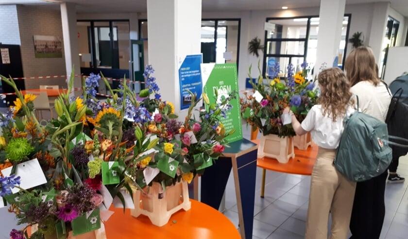 <p>Leerlingen van Het Hooghuis maken een keuze uit het aanbod aan bloemen.</p>