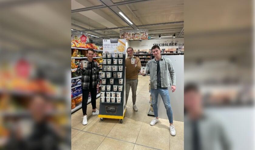 <p>De drie studenten bij een display met de door hun bedachte Snecco-chips.</p>