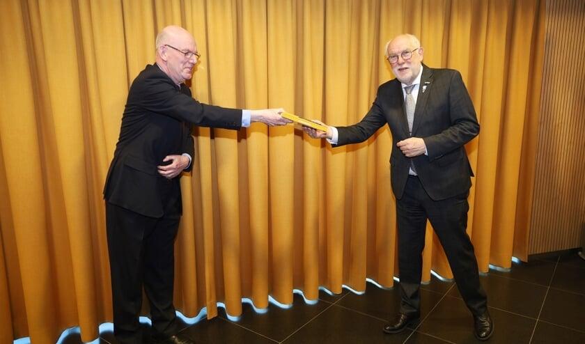 v.l.n.r.: Voorzitter van BING Wim Goossens reikt het eerste boek uit aan burgemeester Karel van Soest.