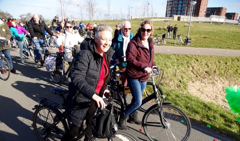 Wethouder Van Tatenhove en initiatiefnemer Silvia Wessels nemen samen met leerlingen van De Poolster al zingend het Zangfietspad in gebruik.