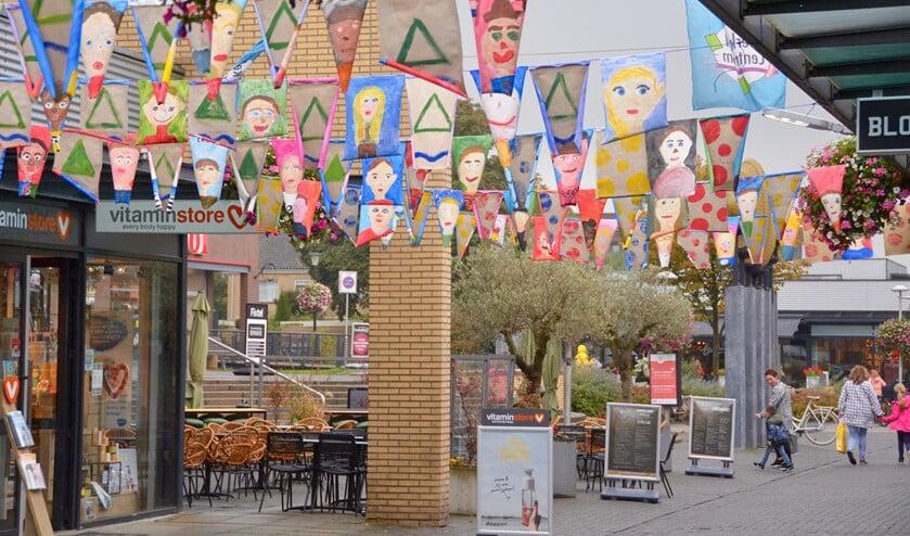 De vlaggetjes in het centrum van Berkel kunnen gelukkig tegen regenachtig weer.