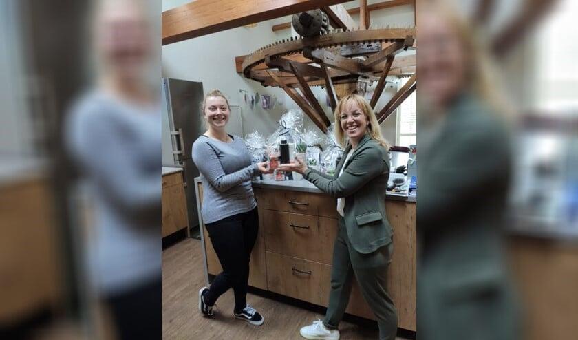 <p>Teamleider Femke de Bruijn (rechts) overhandigt het eerste pakket aan haar collega Celina.</p>