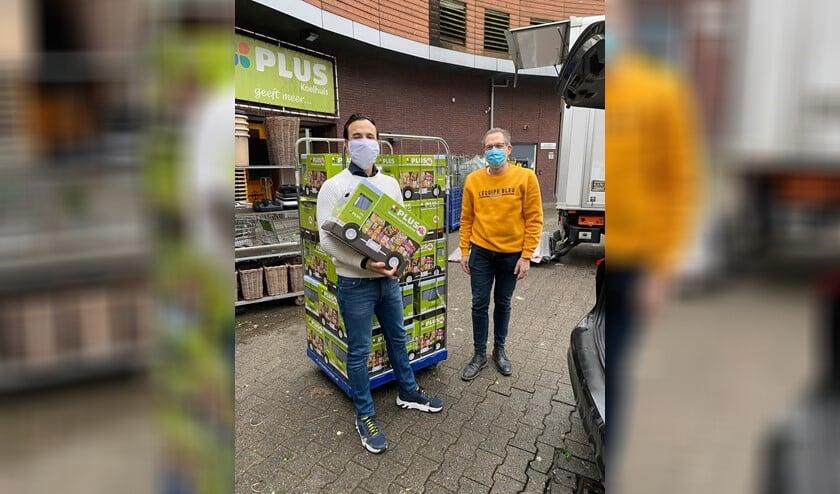 <p>Jordy Koelhuis (links) en Wim de Heer in de weer met de 125 pakketten.</p>