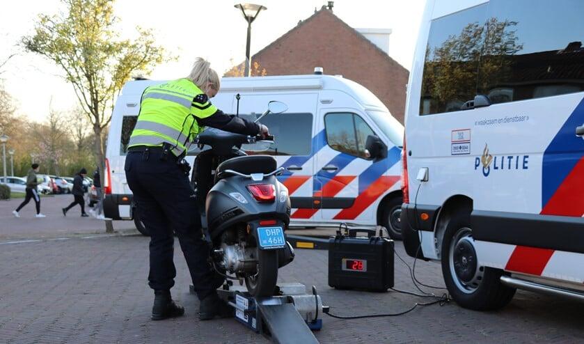 <p>Een agent controleert de maximum snelheid van een scooter op een zogenoemde rollerbank. (Foto: Spa Media)</p>