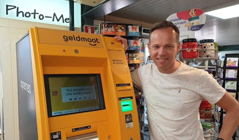 Boekhandelaar Mark Snoek bij de nieuwe geldautomaat.