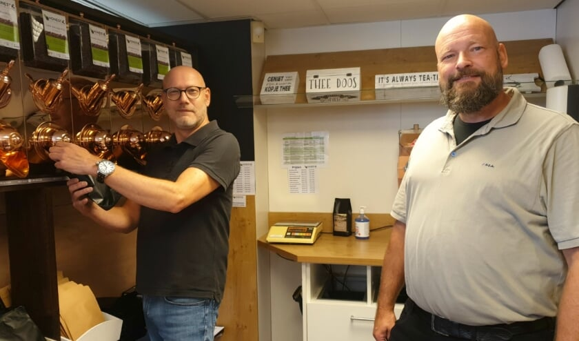 Jan Koster en Wim Bergsen bij de koperen koffiewand.