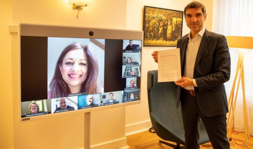 <p>Staatssecretaris Paul Blokhuis met de brandbrief, digitaal in gesprek met wethouders jeugd. </p>
