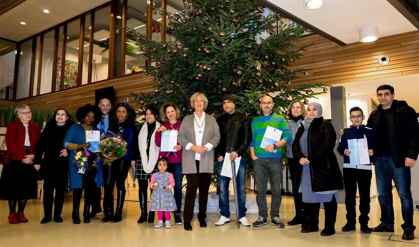 Een deel van de nieuwe Nederlanders met burgemeester Driessen (midden) en wethouder McDaniel (4e van rechts). | Foto: J.P. Kranenburg