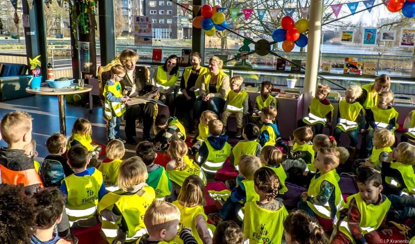 De peuters hangen aan de lippen van burgemeester Driessen die 'De kleine walvis' voorleest. | Foto: J.P, Kranenburg
