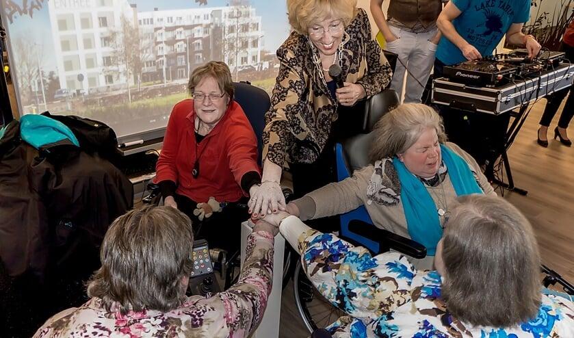 Burgemeester Driessen verricht de officiële openingshandeling samen met bewoners Tanne Wondergem (met blauwe sjaal), Corrie Cats, Irene van Leeuwen en Caroline Kuijt.   Foto: J.P. Kranenburg