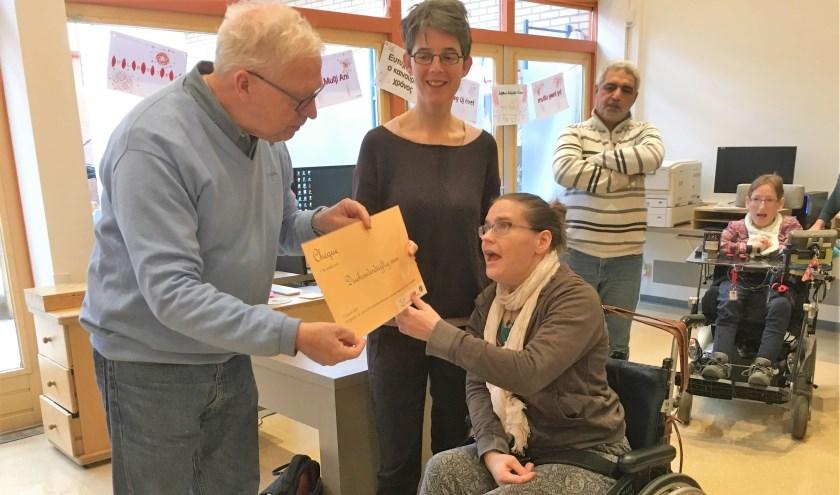 Bob Reidsma overhandigt de cheque aan een cliënt van Gading. In het midden staat locatiemanager Marjolein de Groot van Gading.   Foto PR