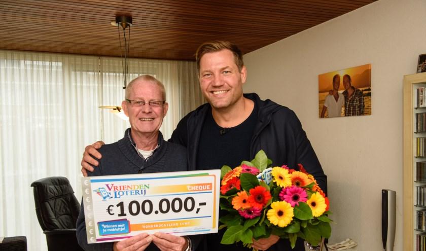 Johannes uit Leiderdorp wint 100.000 euro bij de VriendenLoterij en ontvangt een cheque uit handen van VriendenLoterij-ambassadeur Dennis van der Geest.  