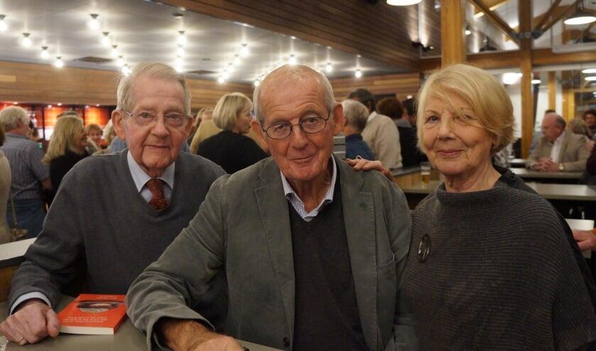 Har Meijer (midden) signeert een boek voor twee dorpsgenoten.