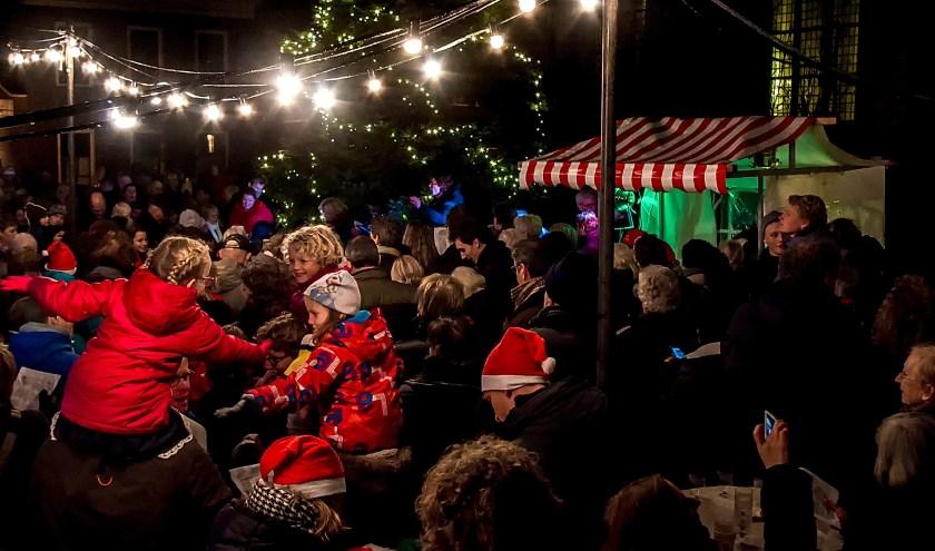 Samenzang bij de kerstboom in de tuin van de dorpskerk. | Archieffoto: J.P. Kranenburg
