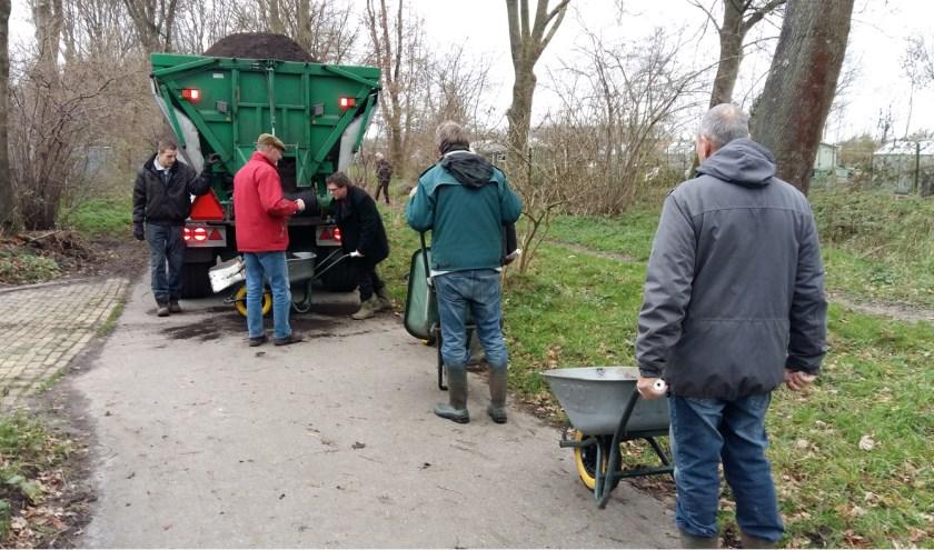 Vrijwilligers van de schooltuinen halen kruiwagen na kruiwagen compost die vervolgens over de tuinen wordt uitgespreid. | Foto: PR