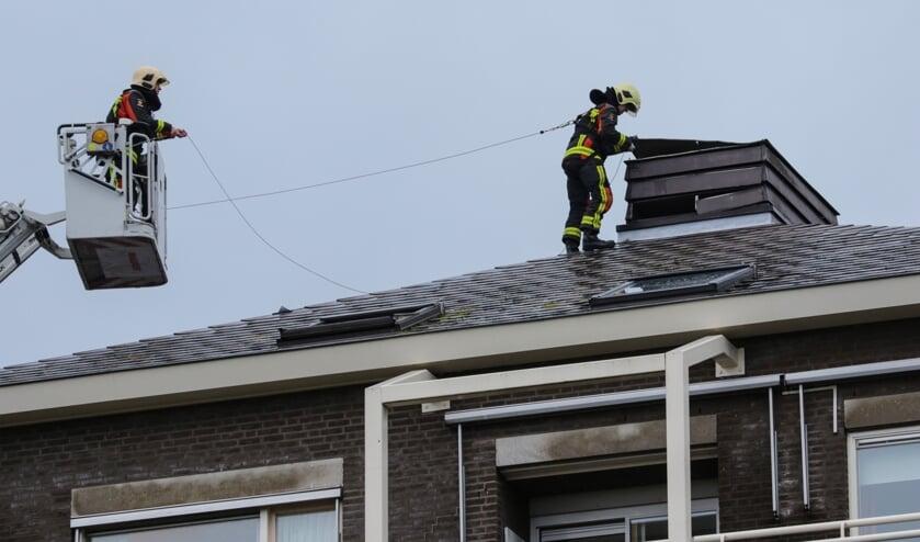 Brandweerlieden proberen de loszittende platen weer vast te krijgen. Foto: AS Media
