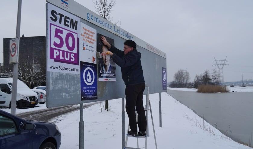 Jan Meijles plakte zondag de GroenLinks posters op de verkiezingsborden.