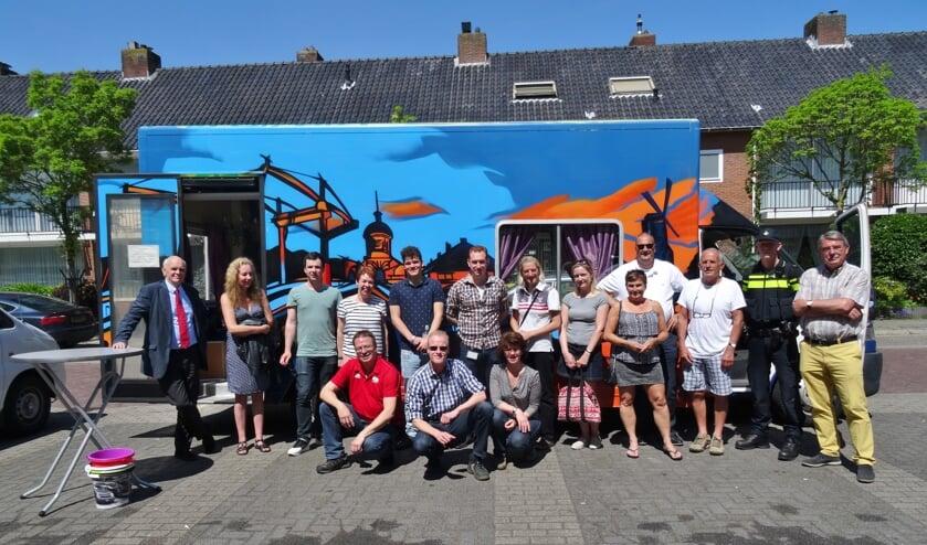 Oranjewijkbewoners en gemeenteambtenaren voor de nieuwe buurtbus, die zal dienen als verzamelpunt bij de wijkwandelingen.