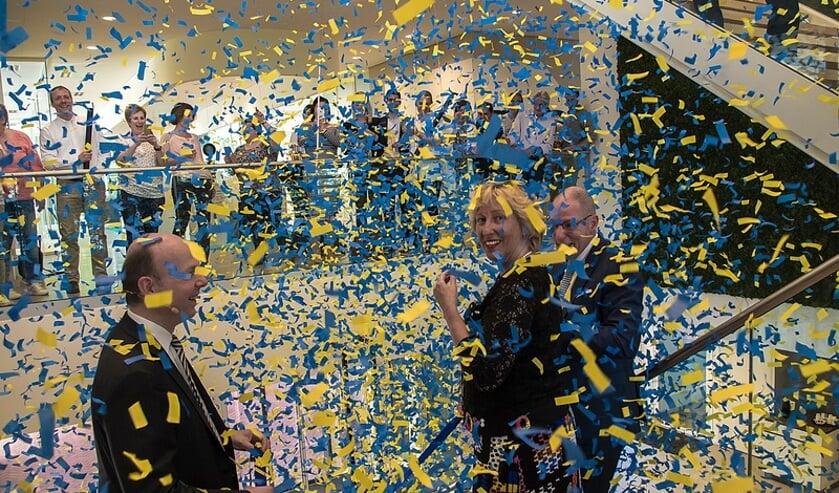 V.l.n.r. Michael Speiser, directielid van Olympus Europa, burgemeester Laila Driessen en Henk Braat, algemeen directeur van Olympus Nederland, in een regen van confetti.   Foto: J.P. Kranenburg