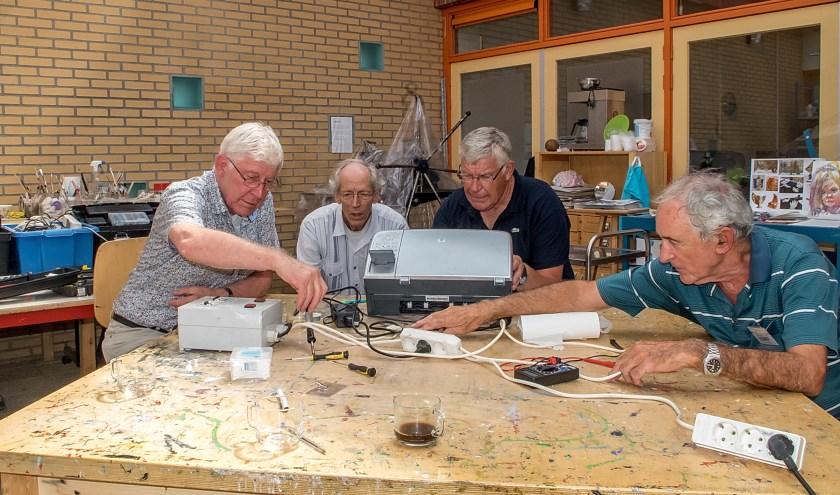 Vrijwilligers van het Repair Café buigen zich over een haperende printer.