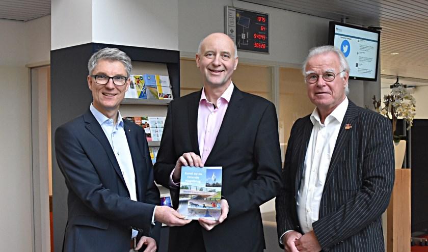 Nic van Tilborg (l.) en Siebe Stellingwerff Beintema overhandigen het boekje aan wethouder Arno van Kempen.   Foto: Piet van Kampen