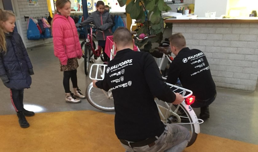 De mannen van Halfords checken een fiets terwijl de eigenares geïnteresseerd toekijkt.