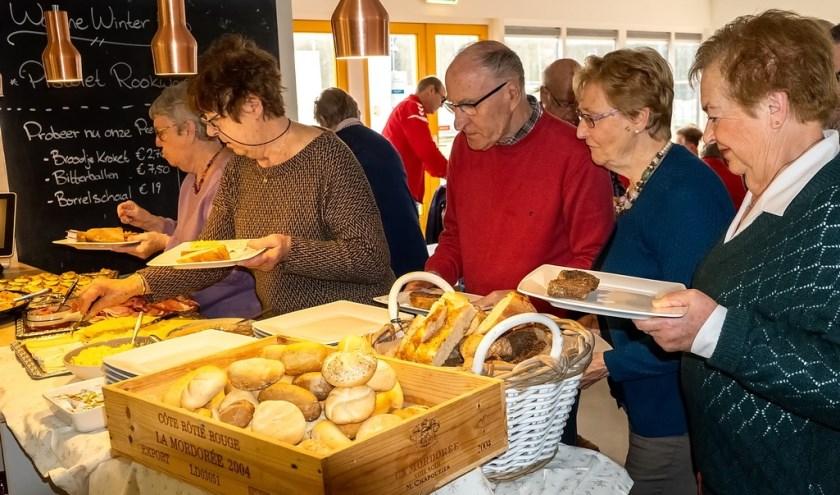 In de rij voor het goed gevulde buffet van de kerstlunch van Clubhuis De Derde Helft.
