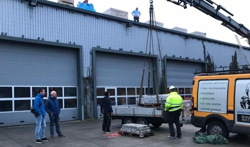 Bestuursleden Coen Huisman en Lodewijk van Aernsbergen van Zon op Leiderdorp kijken toe hoe de medewerkers van Freek van Os alle benodigde materialen op het dak takelen.