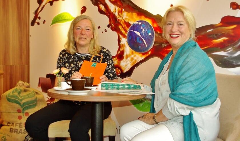 Marjolijn van der Jagt overhandigt de eerste Terug naar Oegstgeest-stickers aan Karen Welter van de Koffiemeulen.