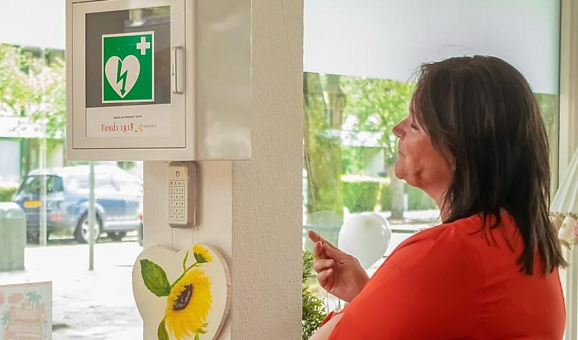 Wethouder Beekhuizen onthult de AED. Onder het apparaat een beschilderd hart, gemaakt door een 86-jarige bezoeker van 't Buurthuis.